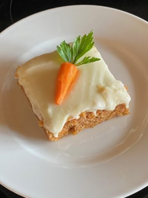 Piece of carrot cake with mini carrot on top.