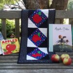 apple books with quilted apple runner and apples on library bench