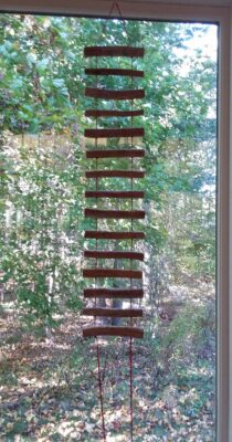 wood and red string ladder art mini in front of window