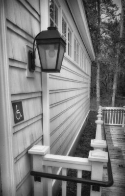 Photo of side entrance at Friend Memorial Library in Brooklin Maine. Close up of the handicap access sign and side lamp with the ramp in the background. Photo by Steve Greenberg
