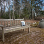 Photo of cedar bench outside Friend Memorial Library in Brooklin, ME with a book on it.