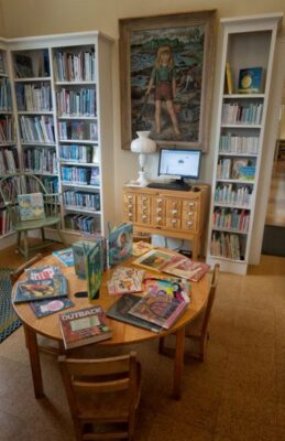 Photo taken inside the Friend Memorial Library Children's Room which highlights the computer card catalog, large oil painting of a girl clamming and many books in the background. by Steve Greeberg