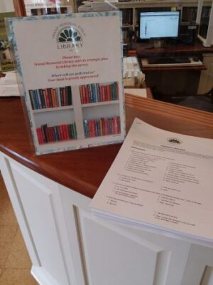 photo of sign asking people to fill out a library survey and the survey on the circulation desk